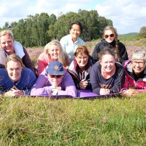 9 glada kvinnor på en ljunghed. Alla uppfyllda efter en underbar yogavandring.